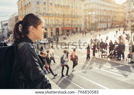 Young traveler woman admiring beautiful sunny Praca de Luis Camoes square in Lisbon, Portugal.Sunny day in Lisbon, perfect place for traveling in Europe.Crowded Lisbon streets.Backpacker photographer