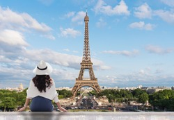Young traveler woman in white hat looking at Eiffel tower, famous landmark and travel destination in Paris, France in summer