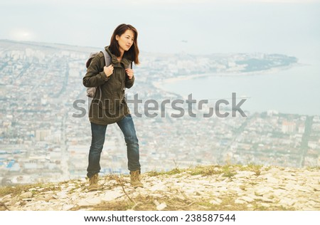 Young traveler woman with backpack walking in highlands over the city. Hiking and recreation theme