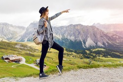 Young traveler woman with  hat and backpack enjoying amazing mountain view , walking and explore nature . Looking  forward . Shows a finger to the top.