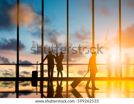 Young travelers dragging suitcases walked to travel abroad in the bus terminal would leave the country over blurred other travelers waiting plane and city at night interior with large windows. #599262533