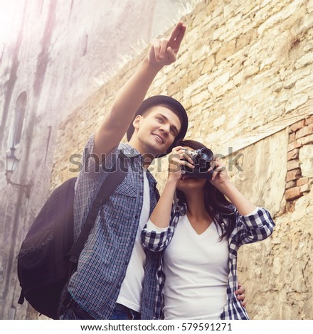 Young traveling couple: taking pictures of old town. Vacation, summer, holiday, journey: concept.
