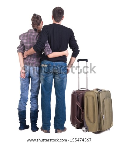 Young traveling couple with suitcas looks where that. back view people. Isolated over white.