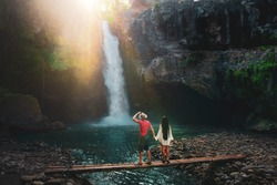 Young traveling multi-race couple explore waterfall in Bali, love story, people in love, vacation in Asia