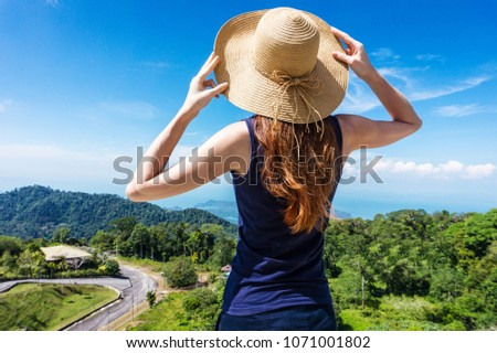 Young traveling woman wearing hat and standing on the top of the mountain cliff with relaxing mood and watching beautiful view of woods and blue sky and clouds on vacation. Travel vacation concept. #1071001802