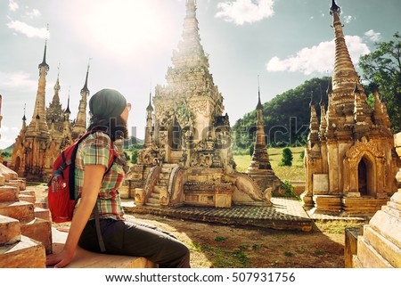 Young traveller enjoying a looking at Buddhist stupas. Burma, Asia. 