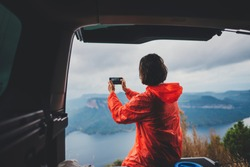 Young traveller girl in red rain coat making photo of beautiful landscape with mountains and lake on modern smartphone while sitting in a car, Happy hiker woman hiking in rain, journey concept