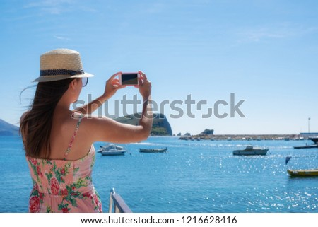 Young travelling woman in hat taking photos of summer sunny sea with smartphone camera. Brunette girl making photography on summer vacation #1216628416