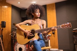 Young trendy black woman with long curly hair sitting playing guitar in a recording studio with a smile of pleasure in close up