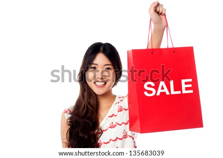 Young trendy girl holding up shopping bag. Year end sale begins.