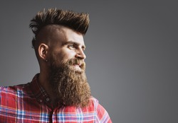 Young trendy man portrait. Punk styled man with Mohawk hairstyle is smiling. Isolated on gray background