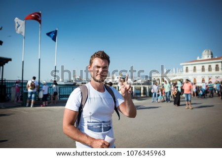 Young trendy man stands on the city square and shows gesture. Serious guy on background of ferry terminal and local people. #1076345963
