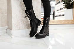 Young trendy woman in black stylish jeans in fashionable leather lace-up boots stands on the white tile in the mall. Fashion collection of women's autumn shoes. Close-up of female legs in footwear.