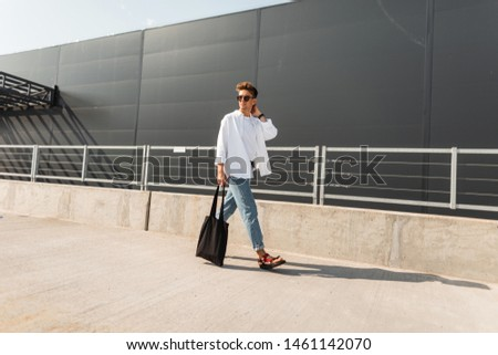 Young trendy young man walks on the city on a sunny day. Handsome hipster guy in fashionable clothes in summer shoes with a bag in sunglasses is traveling near a gray building. Summer youth look. #1461142070