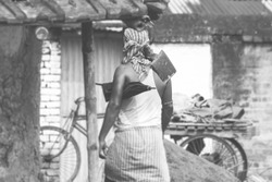 Young tribe farmer walking on the street with a digging hoe