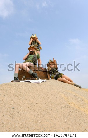 Young twin sisters and an adult girl dress up as explorers. They pose on a sand dune hill dressed with jungle hats and khaki safari clothes. #1413947171