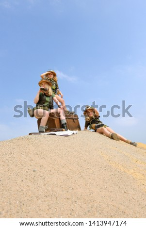 Young twin sisters and an adult girl dress up as explorers. They pose on a sand dune hill dressed with jungle hats and khaki safari clothes. #1413947174