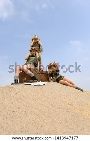 Young twin sisters and an adult girl dress up as explorers. They pose on a sand dune hill dressed with jungle hats and khaki safari clothes. #1413947177