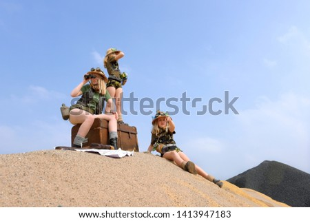 Young twin sisters and an adult girl dress up as explorers. They pose on a sand dune hill dressed with jungle hats and khaki safari clothes. #1413947183