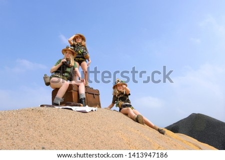 Young twin sisters and an adult girl dress up as explorers. They pose on a sand dune hill dressed with jungle hats and khaki safari clothes. #1413947186