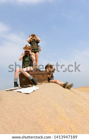 Young twin sisters and an adult girl dress up as explorers. They pose on a sand dune hill dressed with jungle hats and khaki safari clothes. #1413947189