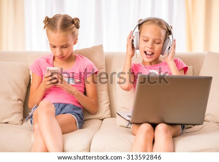 Young twins sisters are using laptop, headphone and smartphone sitting on the couch.