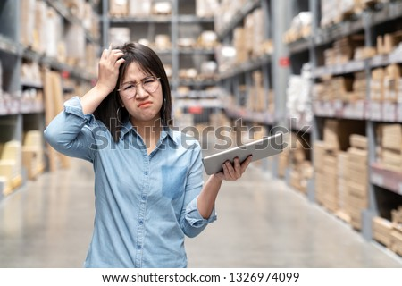 Young unhappy asian woman, auditor or employee looking and feeling confused in warehouse store. Portrait of young girl scratching her head, puzzled face and expressing doubt or uncertainty with work.