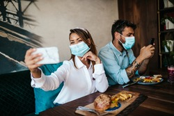 Young unhappy heterosexual couple with face protective masks sitting in modern restaurant and preparing for meal. Coronavirus food and drink concept.