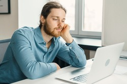 Young unhappy man office worker feeling bored at work, looking at laptop with demotivated face expression while sitting at workplace in office, distracted male worker feeling tired of monotonous job