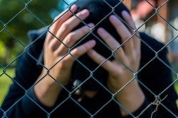 Young unidentifiable teenage boy  holding hes head at the correctional institute ,conceptual image of juvenile delinquency, focus on the wired fence.