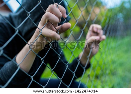 Young unidentifiable teenage boy holding the wired garden at the correctional institute, conceptual image of juvenile delinquency, focus on the boys hand. #1422474914