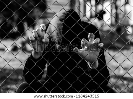 Young unidentifiable teenage boy holding the wired garden at the correctional institute in black and white, conceptual image of juvenile delinquency, focus on the boys hand. #1184243515
