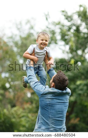 Young unidentified dad in casual clothes raised laughing little boy in the arms against background of blurry trees