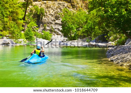 Young unidentified sportsman kayaking along mountain river in sunny summer day