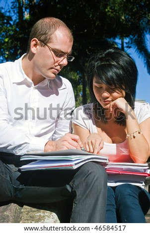 Young university professor explaining something to one of his students on a beautiful day