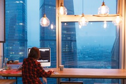 young unknown female office manager working in the creative studio in the evening and sitting at computer on window background with view of giant skyscrapers