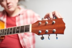 Young unknown man tuning a guitar, detail shot, focus in the hand and the headstock.