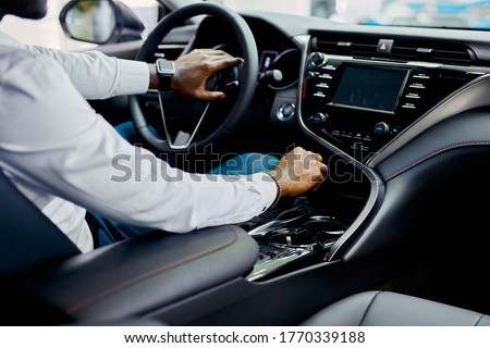 young unrecognizable businessman sitting in luxurious automobile, new owner of car Foto stock ©