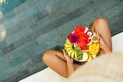 Young unrecognizable woman by the pool with a plate of tropical fruits: watermelon, pineapple, bananas, mangosteen, passion fruit, mango and dragon fruit. Bali Indonesia.