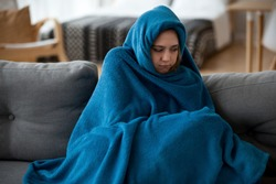 Young unsatisfied sick woman covered with warm blue blanket plaid from head to toes sitting alone on couch in living room at cold home. Seasonal problems, virus diseases and central heating concept