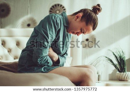 Young upset stressed woman suffering from abdominal and stomach pain during menstruation, PMS in room at home. Inflammation and infection. Food poisoning