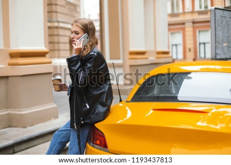 Young upset woman in leather jacket with cup of coffee to go leaning on yellow  sport · Beautiful Brunette ... 2f5f81af7