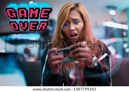 Young urban Asian gamer girl playing mobile games on smartphone device - Female player losing online wireless multiplayer phone game with game over graphic - app, entertainment and lifestyle concept #1487799263