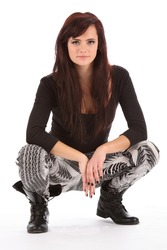 Young urban dance girl in black boots crouching