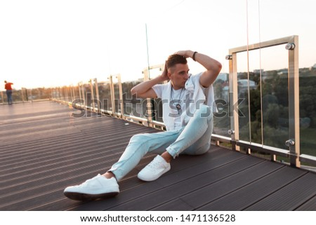 Young urban man with a stylish hairstyle in a stylish T-shirt in vintage jeans in white sneakers posing while sitting on a wooden floor on the terrace. Attractive guy model is enjoying the sunset.