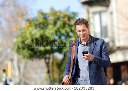 Young urban professional man using smart phone. Businessman holding mobile smartphone using app texting sms message wearing jacket on Passeig de Gracia, Barcelona, Catalonia, Spain. #182035283