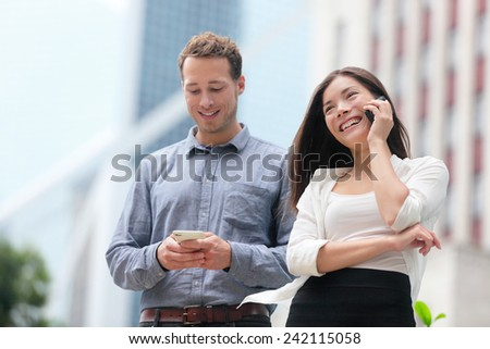 Young urban professionals business people on smartphones in Hong Kong. Businessman using app on smartphone and businesswoman talking having conversation on smart phone in Hong Kong Central.