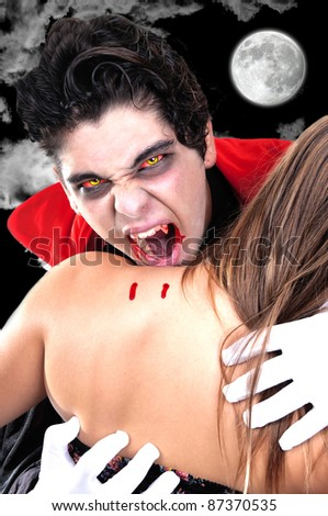 young vampire biting his woman  in the nigth - stock photo