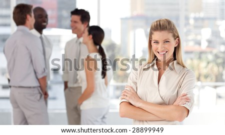 Young vibrant Business woman in front of a group of associates smiling