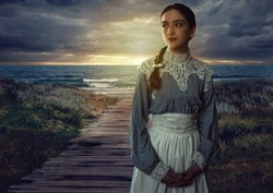 Young victorian girl in white dress and blue striped blouse on the coast at sunset.